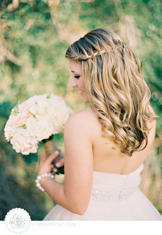 Elegant bride looking over shoulder with pink and white bouquet and waterfall braided hair.