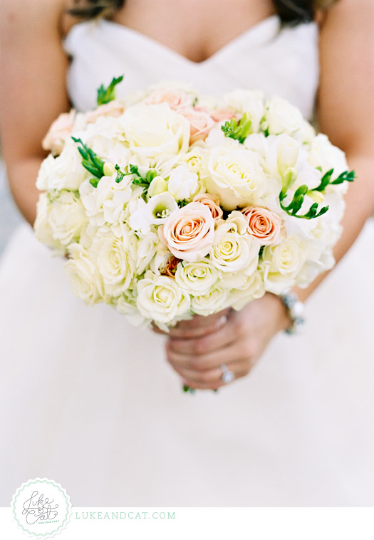 Wedding bouquet with white and pink roses being held by the bride.