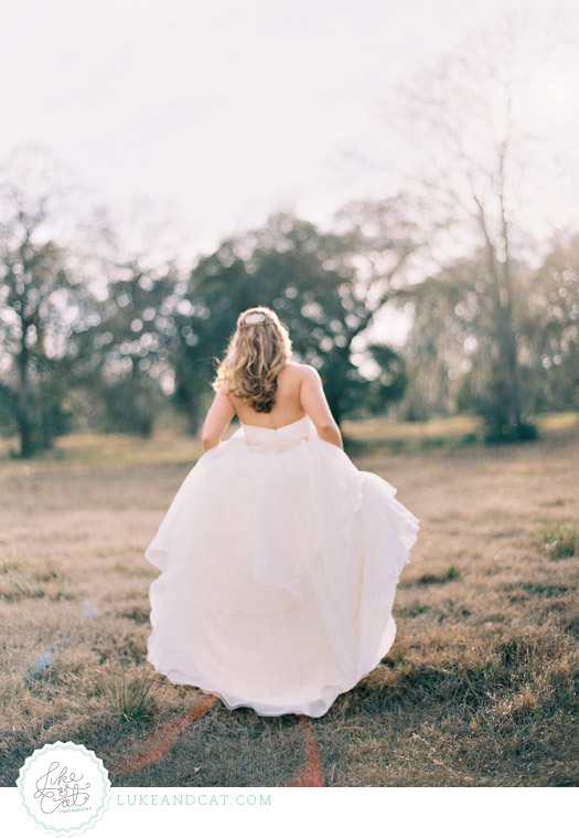 Bride holding her dress and walking away in the golden sunlight.